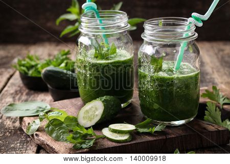 Fresh green smoothie with straws on a wooden tablehealthy vegan food