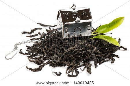 Strainer from silver metallic into house shape with small chain for preparing of tea dry black tea and green leaves isolated on white background.