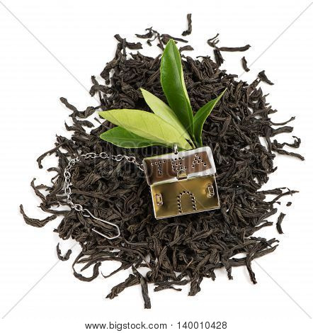 Top view of dry black tea and green leaves and strainer from silver metallic into house shape with small chain for preparing of tea isolated on white background.