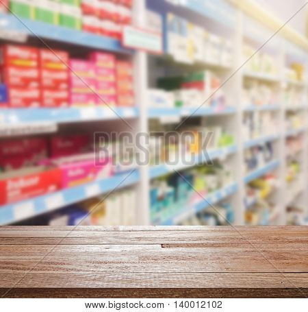 Wood table counter top on blurred shelves pharmacy store, Can be use for display or montage you product