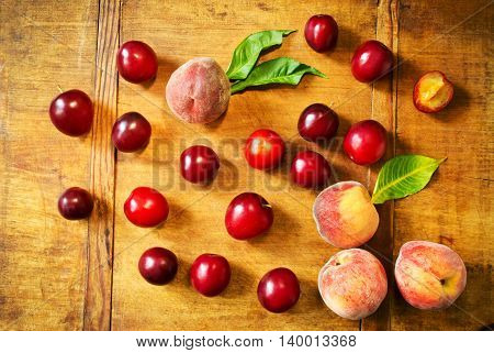 Fresh plums and peaches on a wooden kitchen table