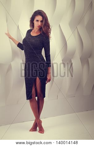 Sexy Woman In Fashion Grey Dress Posing Near The Paper White Wall. Full Length Portrait Without Shoe