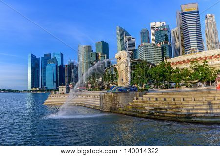 SINGAPORE-JULY 9 2016: Merlion statue fountain in Merlion Park and Singapore city skyline at night on July 8 2016. Merlion fountain is one of the most famous tourist attraction in Singapore.