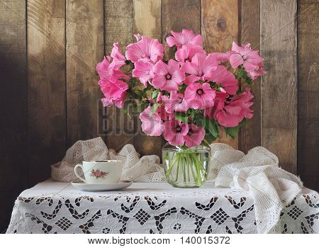 Still life with pink bouquet and Cup on table with white tablecloth with lace. Rustic style.
