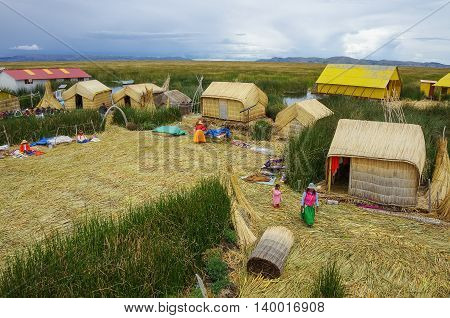 Titicacaб Peru- January 4, 2015 - Local people in traditional attires working near houses at Uros islands on Lake Titicaca.