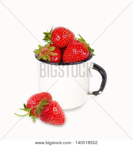 Fresh ripe red strawberries in enamel mug over white background