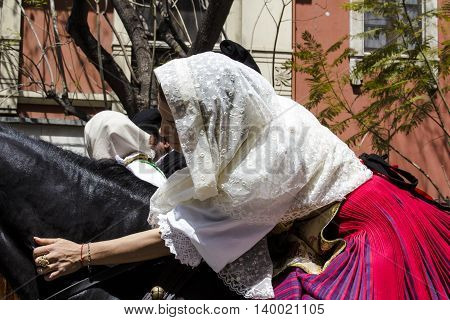 CAGLIARI, ITALY - May 1, 2016: 360 ^ Sant'Efisio Festival - Sardinia - portrait of a beautiful girl in traditional Sardinian costume caressing her horse