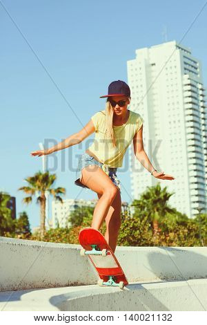 Beautiful girl riding on a skateboard and making tricksin sunny weather