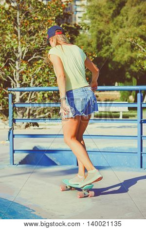 Beautiful girl riding on a skateboard in sunny weather