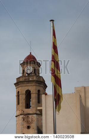 Church Bell Tower in Calella evening. In the foreground of the Catalan flag