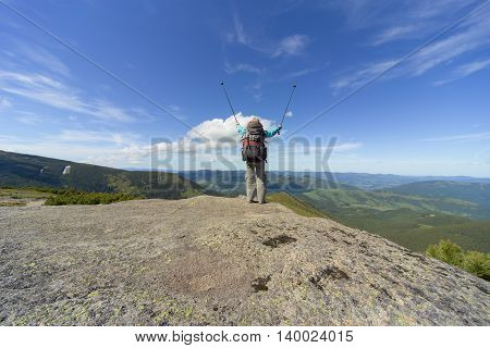 The girl in the campaign stands on a rock in the mountains against the blue sky.