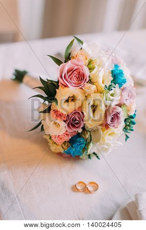 Close-up of bridal bouquet with pair golden wedding rings.