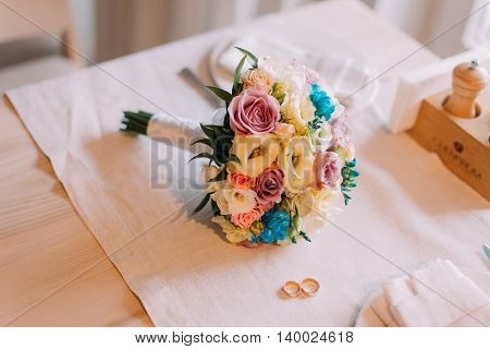 Close-up of beautiful bridal bouquet with two golden wedding rings.