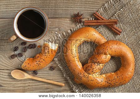 Cup of hot coffee with tasty pretzels for breakfast on wooden table top view