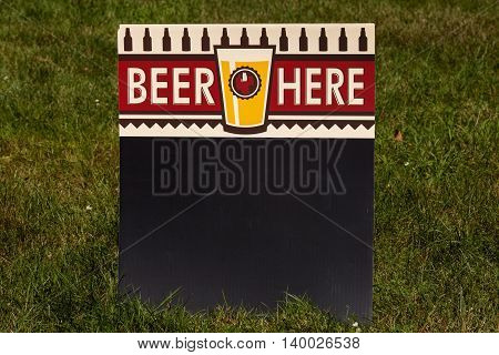 A beer here sign sitting in the grass
