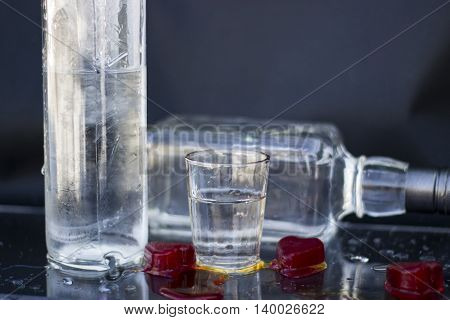 Vodka bottle with glasses and a red ice vodka and whiskey in glass with ice alcoholic drink