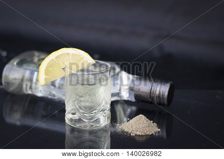 A glass of vodka with ice and lemon on a black background black ground pepper