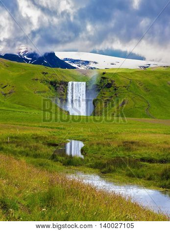 The huge deep falls Skogafoss are reflected in small stream. Grandiose reflection