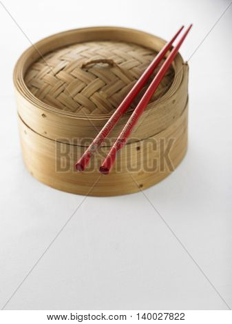 bamboo tim sum steamer with chopsticks on the white background