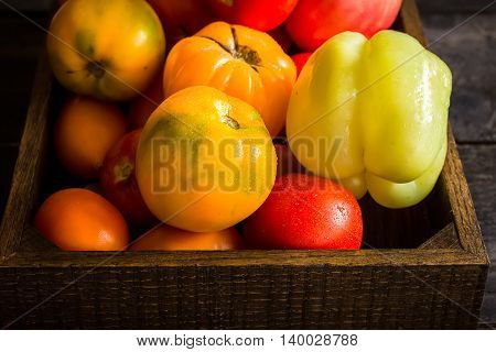Red And Yellow Tomatos In Wooden Box.