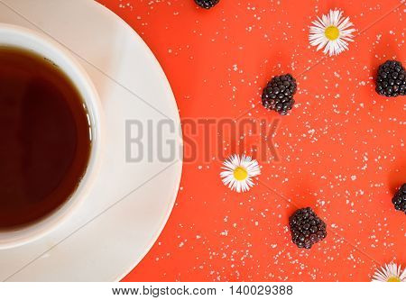 tea cup on a red table with sugar and blackberries