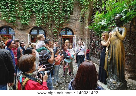 VERONA, ITALY - APRIL 26: Unidentified tourists near Juliet's statue on April 26, 2013 in Verona, Italy. The Juliet's statue is one of most popular and symbolic tourist attraction in Verona, Italy.