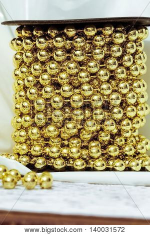 Golden (aureate) balls. Christmas decoration. Chain golden ornamental beads on a reel.