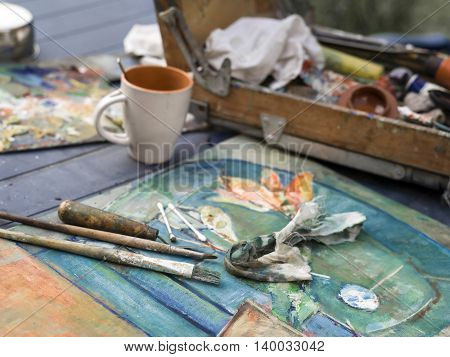 Unfinished art work with paint brushes in focus the easel and cup of tea or coffee in the blurred background