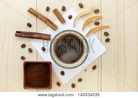 Black coffee with cinnamon sticks and orange peels in a transparent mug top view / sunrise coffee with cinnamon and citrus aroma