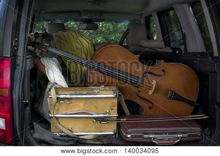 A car trunk loaded with cello and artist equipment outdoor cropped shot
