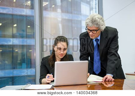 Mature businessman helping a young employee in the office