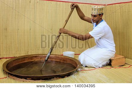 NIZWA, OMAN, MAY 27, 2016: factory worker stirs ingredients in a kettle in the process of making traditional Omani halwa