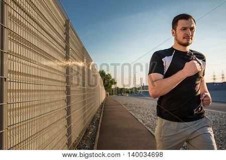 Close-up portrait of athletic man running along beautiful grey wall outdoors, muscular build young runner working out while jogging in the park. Sunset