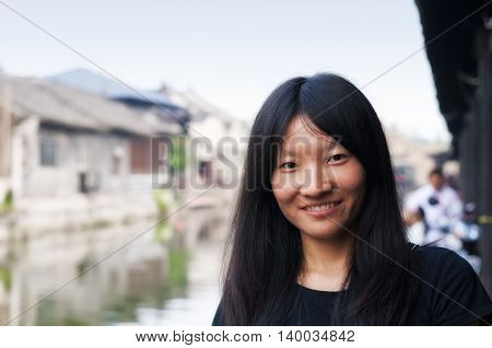 A smiling chinese woman sitting on the edge of a water canal in Fengjing town shanghai China.