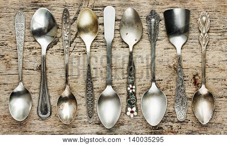 Vintage tea spoons collection on old wooden background top view