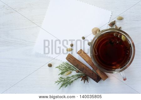 Black tea in a transparent mug with aromatic spices and card for inscriptions top view / warming drink for mood