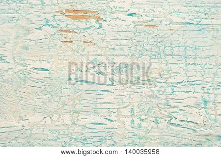 Old shabby wooden surface with cracked blue paint can be used as a background