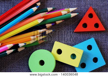 Back to school. Bright colored pencils and bright colored shapes (rectangle, circle, square, triangle) lie on a textured fabric on the table