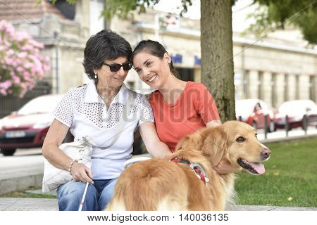 Blind woman and homecarer relaxing on bench