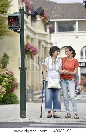 Home carer helping senior woman crossing the street