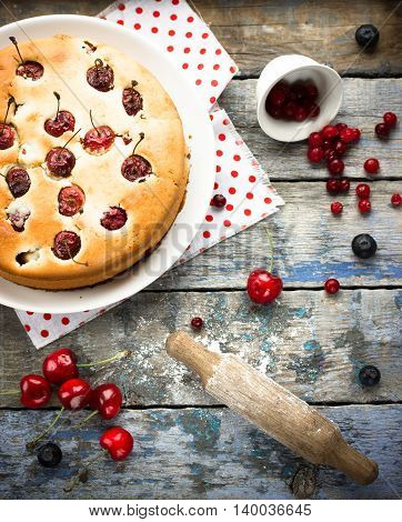 Homemade cherry pie on rustic background top view