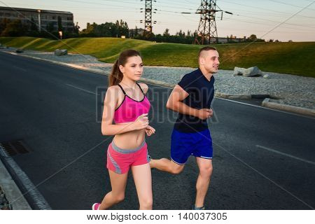 Close-up portrait of athletic couple running on the road, muscular build young runners working out while jogging in the park. Evening