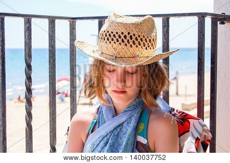 Girl wearing a hat in a balcony in front of the beach