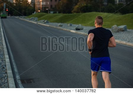 Close-up portrait of athletic man running on the road, muscular build young runner working out while jogging in the park. Evening. view from the back