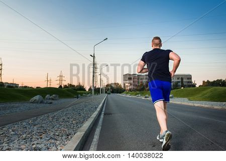 Full length portrait of athletic man running on the road, muscular build young runner working out while jogging in the park. Evening. view from the back