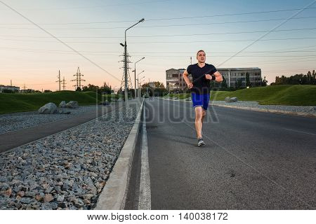 Full length portrait of athletic man running on the road, muscular build young runner working out while jogging in the park. Evening