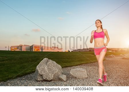 Running woman. Runner jogging in sunny nature. Female fitness model training outside in sunset sky background. with solar flare