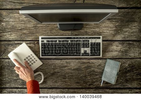 First person view of hand reaching for phone seated in front of computer keyboard monitor and notepad.