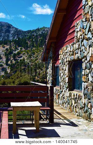 Rustic lodge with outdoor furniture overlooking mountain terrain taken in Mt Baldy, CA