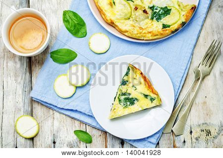 Zucchini Spinach frittata on light wooden background